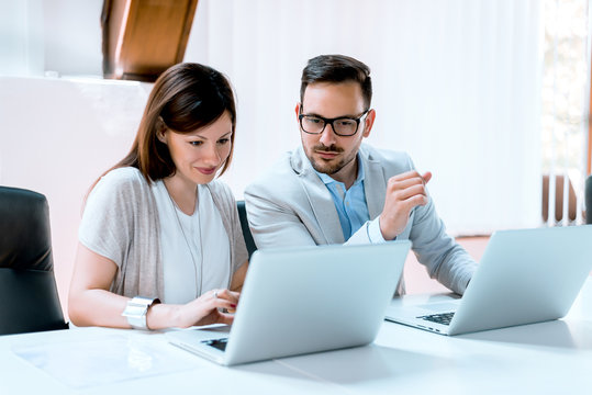 Young businessman discussing with his female colleague, and using a lap top in the office.