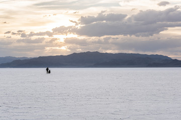 Two people in the distance in the vast salt flats near Salt Lake City, Utah during sunset