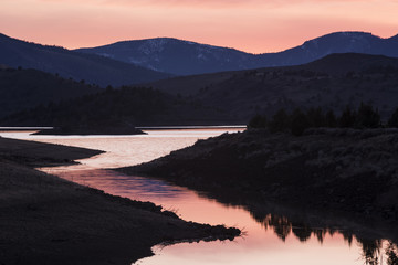 Pink sunset in Weed, California, by a lake near Mount Shasta with hills and meadows
