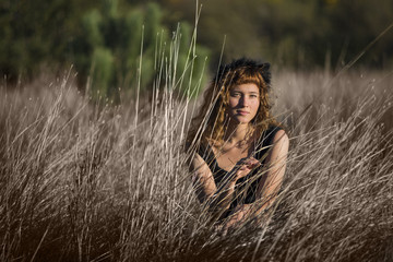 Young female in tall dry hay grass in black dress and ginger hair
