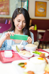 Young Woman taking photo on her dish in restaurant