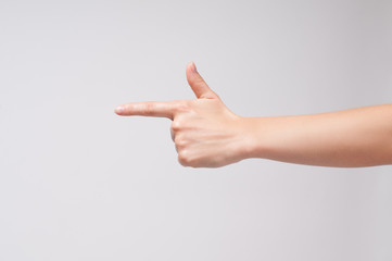 Female hand points a finger at something on white background.