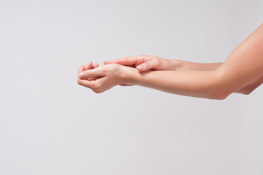 Woman applying cream and massaging on hands