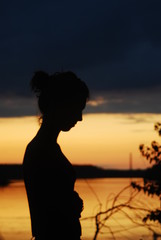 Girl silhouette by the river