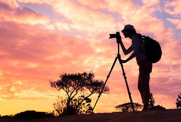 Outdoor adventure concept. Female photographer taking pictures in a beautiful nature setting.