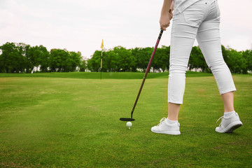 Young woman playing golf on course in summer day