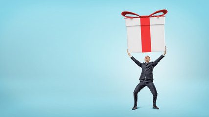 A small happy businessman standing on blue background and holding a giant gift box with both hands.