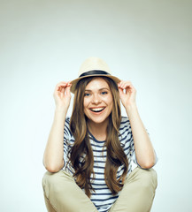 Beautiful young woman sitting relaxed wearing modern hat.