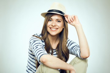 Smiling young woman sitting with folded hands.