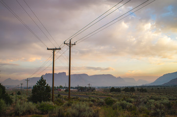 Powerlines with desert cliffs in background