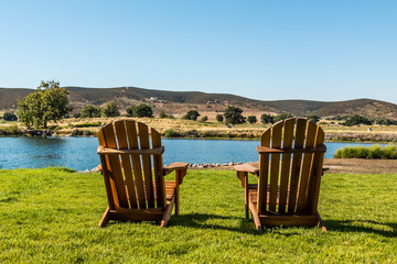 Two Adirondack chairs before a lake in a mountainous valley in San Diego, California.