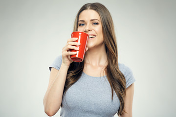 Smiling girl holding big red coffee glass.
