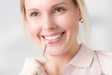 Zahnarzthelferin zeigt, wie die Zahnfarbe für einen Zahnersatz bestimmt wird