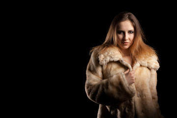Hot sexy woman in fur and bra on black background in studio photo. Erotic attractive model