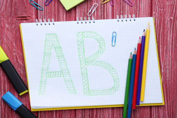 Handwritten letters in notebook with colored pencils on red wooden table