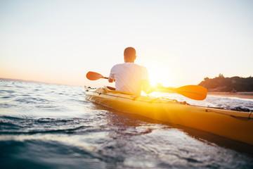 Man kayaker paddling kayak at sunset