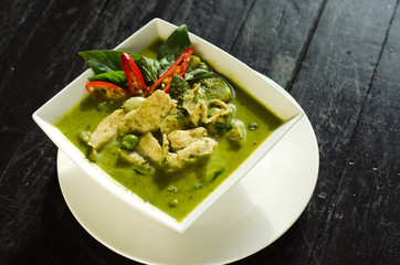 Thai Food: Green curry in white bowl on wood table