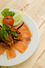 Thai style spicy salmon salad on wood table