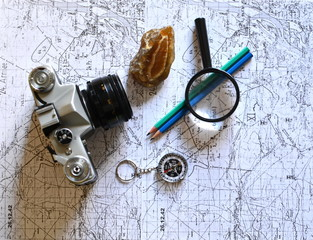 old military topographical map, pencil, vintage photo camera, mineral stone, magnifier and compass