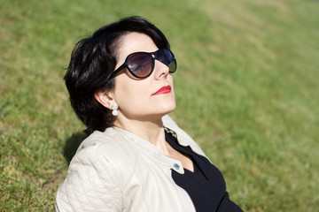 latin woman with sunglasses turning her face toward the sun while relaxing on lawn