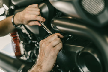 Closeup image of motorcycle mechanic repairing motorcycle in automobile store. Man hands with special tools.