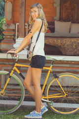 Pretty woman standing with old bicycle outdoors.
