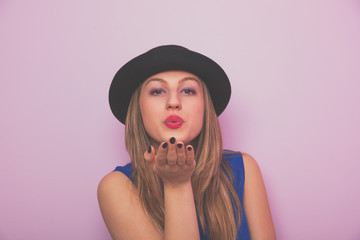 Young attractive girl with hat sending air kiss.