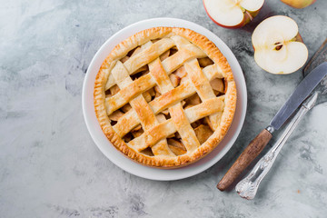 Popular American apple pie on gray table. Homemade classical friut tart. Copy space