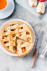 Popular American apple pie and cup of tea on gray table. Homemade classical friut tart. Copy space