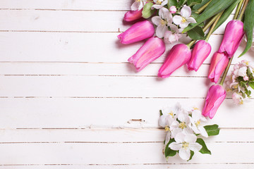 Apple tree flowers and pink tulips  on white wooden background.