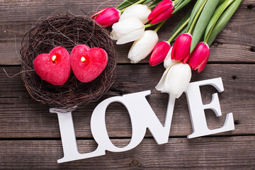 Word love, two red  candles in form of heart in nest and  bright spring flowers on wooden background.