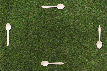 top view of wooden spoons on grass with place for copy space in the middle