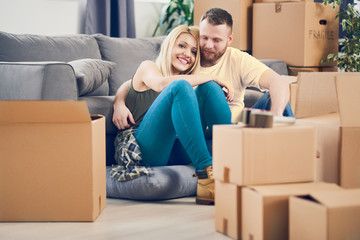 Couple sitting on a floor in new apartment, boxes all around