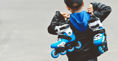Toned baner little beautiful boy with roller skates in his hands
