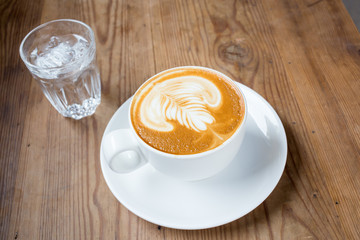 Cup of latte or cappuccino with a glass of water on the table in cafe