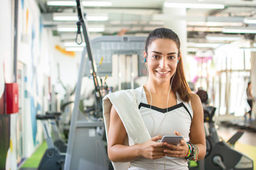 Smiling girl listening to favorite songs on smartphone in gym.