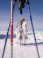 two women with skis smiling at viewer