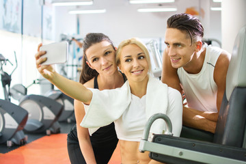 Group of happy young people taking selfie by smartphone in gym.
