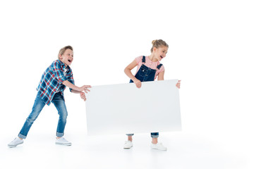 Cheerful cute kids having fun with blank placard isolated on white