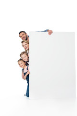 happy family looking out behind blank banner isolated on white