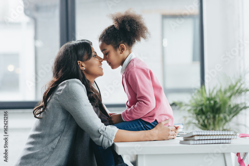 side view of african american mother able to kiss her little daughter