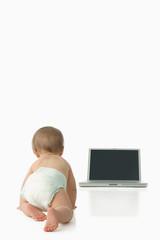 Baby crawling towards laptop