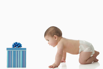 Baby crawling towards gift box