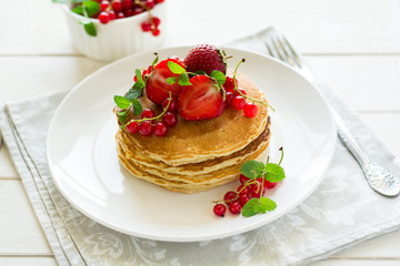 Tradition breakfast: stack of pancakes with berries decorated mint leaves on white wooden table. Selective focus