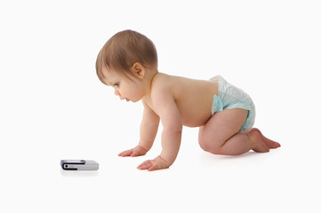 Baby crawling towards mobile phone
