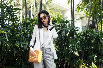 Portrait of beautiful elegant Asian woman fashion model standing outdoors. Wall mural