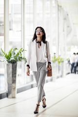 Beautiful elegant smart Asian businesswoman walking at shopping mall and smiling.