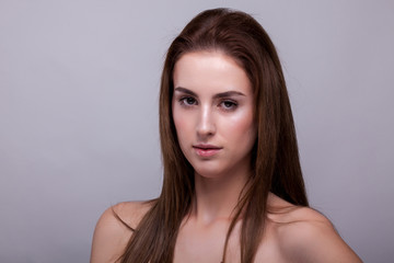 Beauty portrait of woman with no makeup on gray background in studio photo. Beauty and fashion.