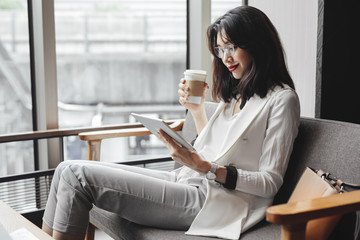 Beautiful elegant Asian businesswoman drinking coffee at cafe and using tablet.