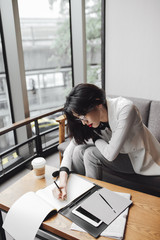 Business woman sitting at coffee shop and writing in notebook